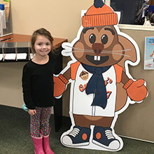 A little girl helping QuiNBy the Savings Squirrel put on his winter clothes.