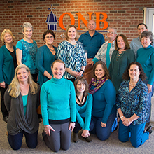 A group of QNB employees wearing teal for Wear Teal Day.