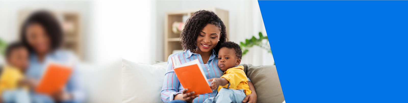 A mother reading a book to her child in their home.